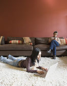 Woman laying on floor using laptop and man sitting on sofa using cell phone — Stok fotoğraf