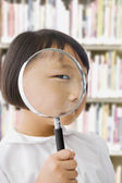 Asian girl in library holding magnifying glass — Stock Photo