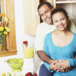 Couple hugging in their kitchen - Stock Photo
