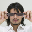 Young Hispanic man holding eyeglasses — Stock Photo
