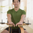 Asian man stretching on exercise equipment — Stock Photo