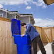 Hispanic man looking in garbage can — Stockfoto
