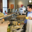 Hispanic cafe owner helping customer — ストック写真