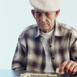 Senior Hispanic man playing dominoes — Stock Photo