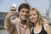 Multi-ethnic couple taking own photograph — Stock Photo