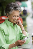 African American woman looking at cell phone — Stock Photo