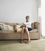 Senior African couple sitting on sofa — Stock Photo