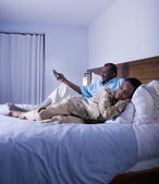 Senior African couple watching television and sleeping — Stock Photo