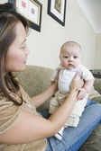 Asian mother holding baby — Stock Photo