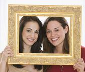 Two young women holding picture frame around faces — Stock Photo