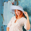 Pregnant woman wearing white dress with big blue hat — Stock Photo #12665769