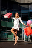 Happy woman shopping and holding bags — Stock Photo