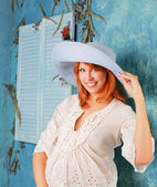 Pregnant woman wearing white dress with big blue hat — Stock Photo