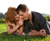Handsome man and woman lying in the grass — Stock Photo