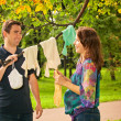 Pregnant couple in park holding baby dress — Stock Photo #12757679