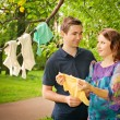 Stock Photo: Pregnant couple in park holding baby dress