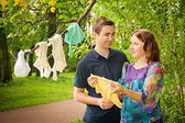 Pregnant couple in park holding baby dress — Stock Photo