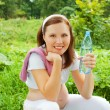 Stock Photo: Pregnant womoutdoor holding bottle of water