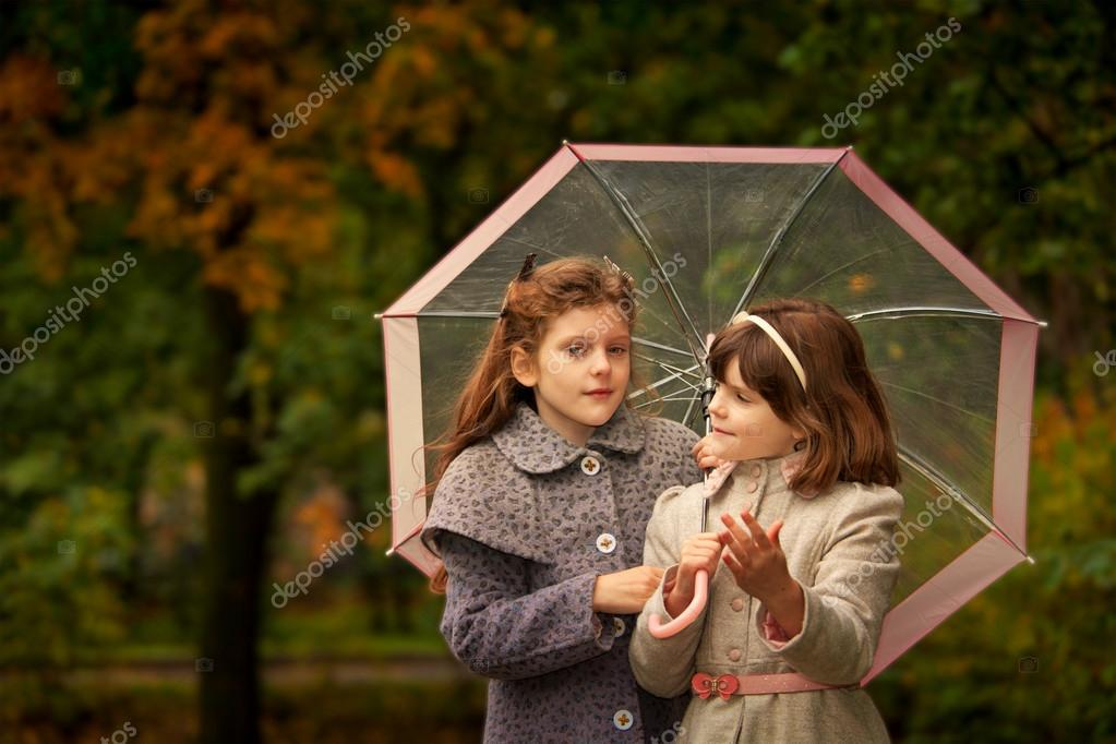 Two girls wearing coats  and felt hats  in autumn park  looking retro style  Stock Photo #13494937