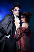 Man and woman wearing as vampire and witch. — Stock Photo
