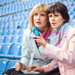 Two excited  women fans watching  competition or concert in stad — Stock Photo