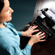 Young woman typing with old typewriter — Stock Photo