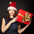 Red hair woman wearing santa hat holding Christmas gift — Stock Photo
