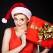 Royalty-Free Stock Photo: Woman wearing santa hat  holding  Christmas gift