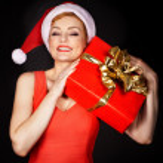 Woman wearing santa hat holding Christmas gift — Stock Photo