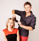 Stylist straitening woman hair by flat iron in hairdresser salon — Stock Photo