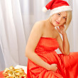 Royalty-Free Stock Photo: Pregnant woman wearing Santa hat and gift