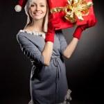 zwangere vrouw dragen kerstmuts en gift — Stockfoto