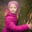 Little girl near tree in autumn or winter park. — Stock Photo