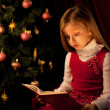Little girl reading magic book near Christmas tree — Stok fotoğraf