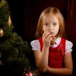 Sorrowful little girl near Christmas tree — Stock Photo