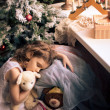 Littlle girl sleeping near Christmas tree — Stock Photo