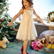 Stock Photo: Little girl trying mothers shoes near Christmas tree. Pretend be