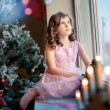 Littlle girl dreaming near Christmas tree — Stock Photo