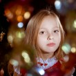 Little blond girl near chrictmas tree . Highlights colorful — Stock Photo