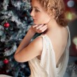 Blond woman wearing santa hat on black background holding shoppi — Stock Photo