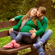Pregnant couple relaxing on the bench - Stock Photo