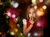 Little girl near Christmas tree with magic irradiance — Stock Photo