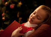 Little girl reading magic book near Christmas tree — Stock Photo
