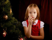 Sorrowful little girl near Christmas tree — Stock Photo