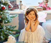 Littlle girl dreaming near Christmas tree — Stock Photo