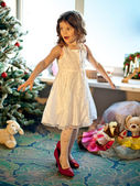 Little girl trying mothers shoes near Christmas tree. Pretend be — Stock Photo