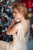 Blond woman wearing santa hat on black background holding shoppi — Stock Photo