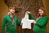 Pregnant couple viewing baby clothes in the park — Stock Photo