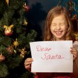 Little girl near Christmas tree and letter for Santa — Stock Photo