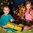 Little boy and girl near Christmas tree and gifts - Stock Photo